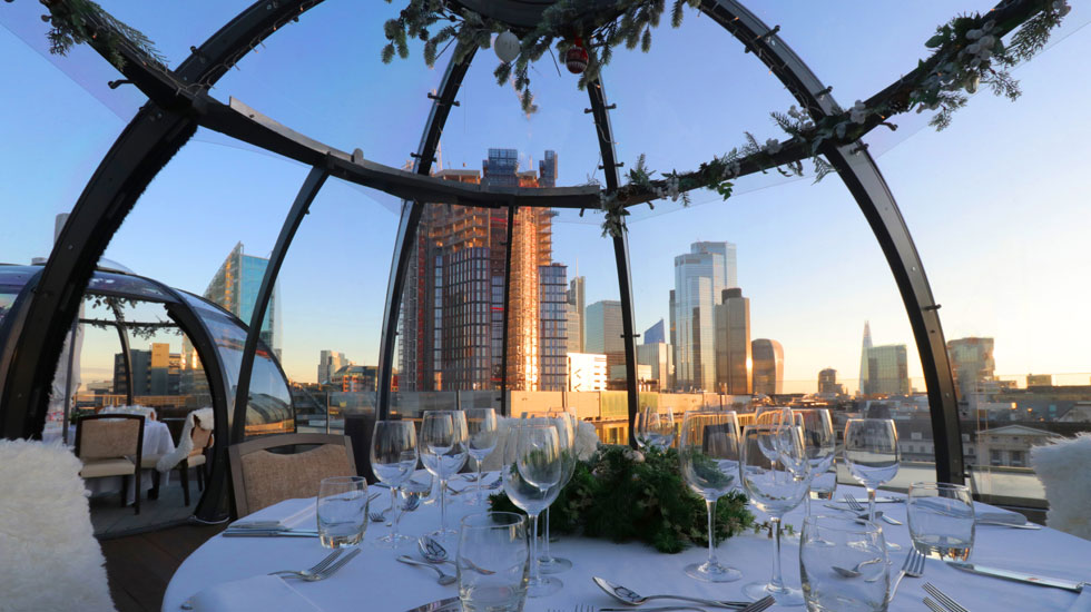 A beautiful evening cityscape view from inside a rooftop dining pod with table set